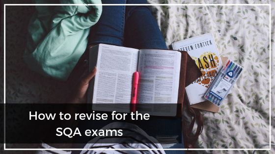 Girl sitting on the bed with an open book and revision tools